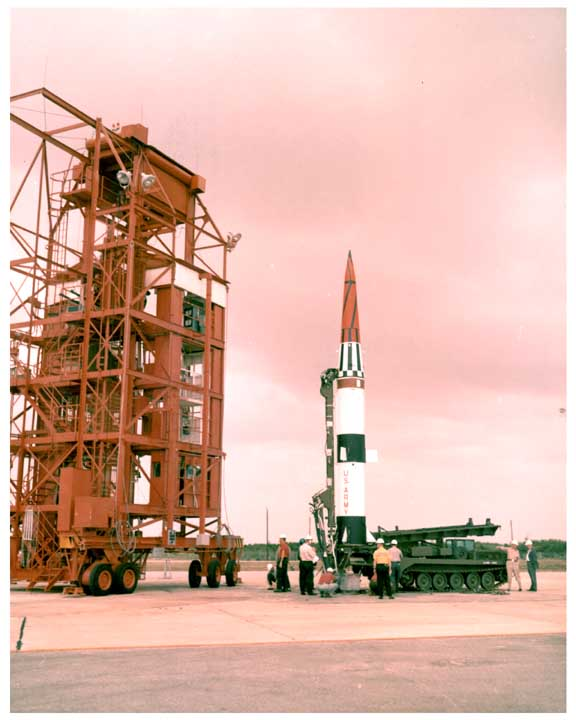 Photo of Pershing missile upright on its track mounted launcher next to a test stand.
