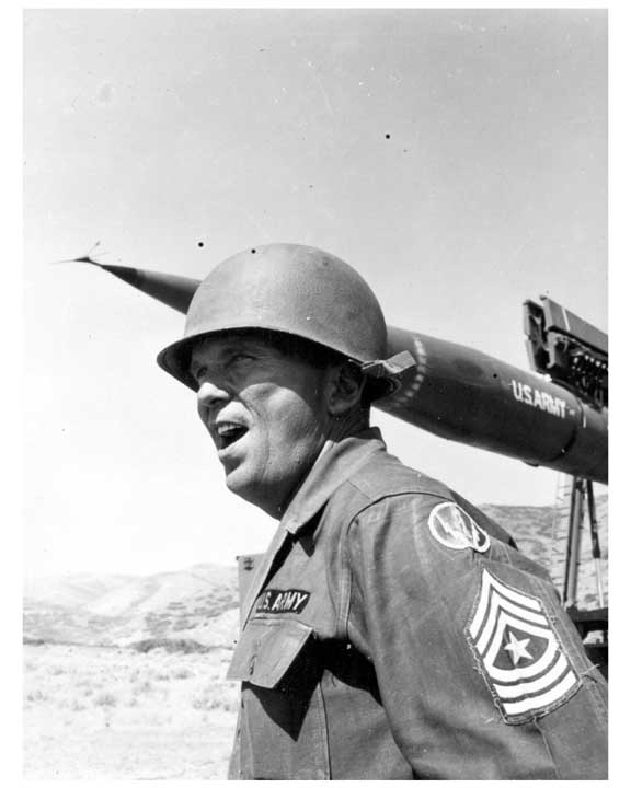 Photo of an Army sergeant major in fatigues and helmet, and in the background the SERGEANT short-range, surface-to-surface missile.